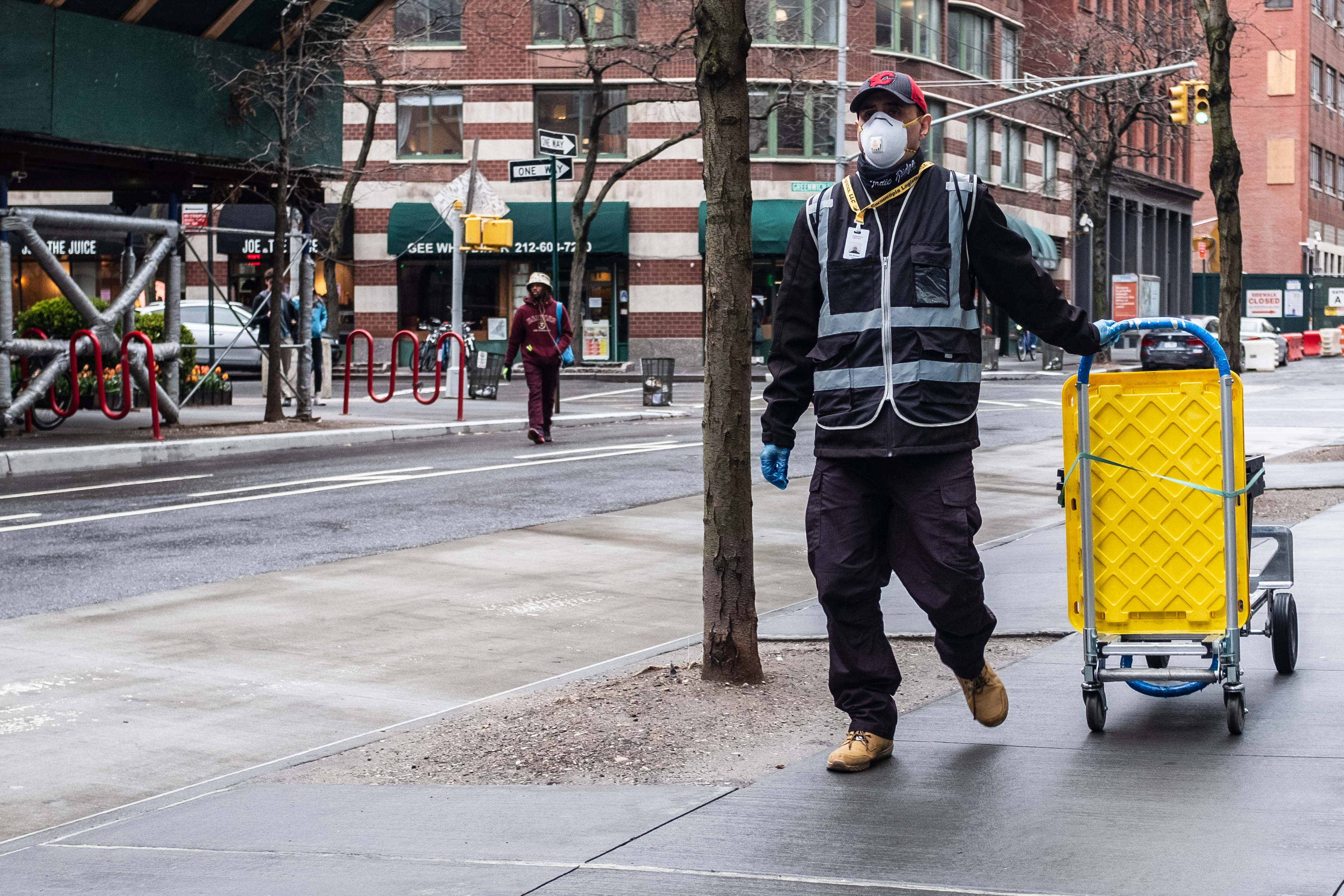 Man wearing a face mask pulls a cart while walking on the sidewalk in New York.